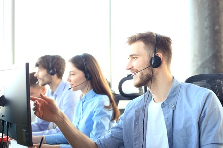 Portrait of call center worker accompanied by his team. Smiling customer support operator at work. 版權商用圖片 - 119854223