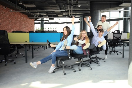 Young cheerful business people dressed in casual clothing are having fun on rowing chairs in a modern office.