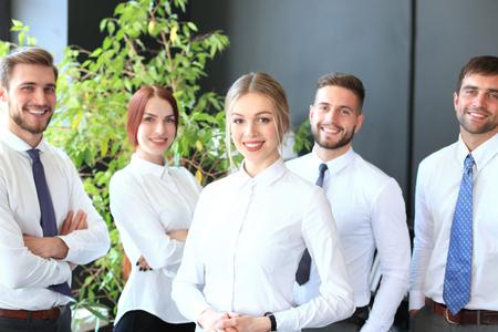 Szczęśliwa młoda kobieta biznesu stojąca przed swoim zespołem