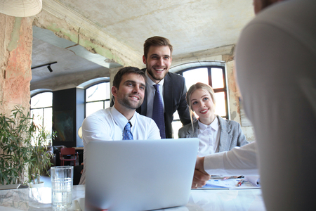 Businessman shaking hands to seal a deal with his partner and colleagues in office Imagens