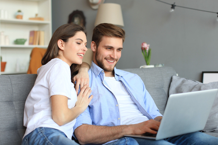Young couple doing some online shopping at home, using a laptop on the sofa