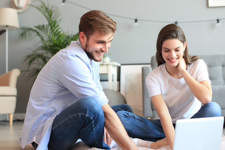 若いカップルは、床にラップトップを使用して、自宅でいくつかのオンラインショッピングを行います 写真素材