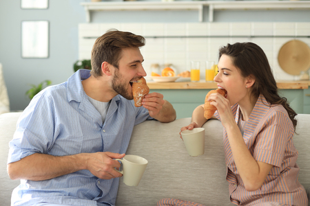 Happy young couple in pajamas in kitchen having breakfast, feeding each other a croissant