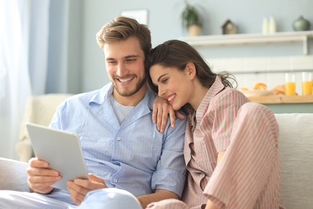 Young couple in pajamas watching media content online in a tablet sitting on a sofa in the living room