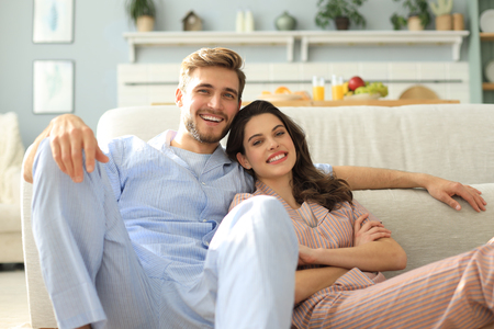 The happy couple in pajamas sitting on the floor background of the sofa in the living room