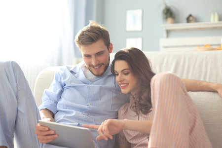 Young couple in pajamas watching media content online in a tablet sitting on the floor in the living room Foto de archivo
