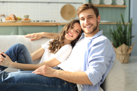 Portrait of cute young couple sitting in sofa 版權商用圖片