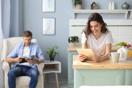Smiling beautiful woman using tablet with blurred man in background at home Фото со стока