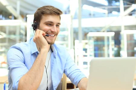 Gelukkige jonge mannelijke klantenservicemedewerker die op kantoor werkt