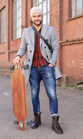 Handsome young man in grey coat and hat walking on the street, using longboard