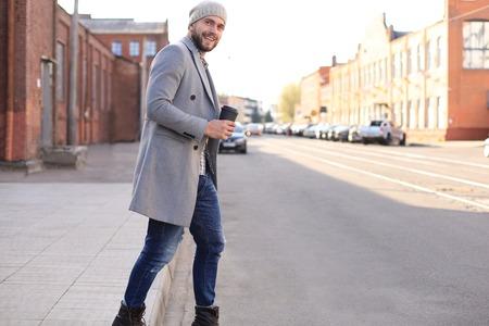 Knappe jonge man in grijze jas en hoed die de straat oversteekt met een kopje koffie