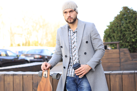 Handsome young man in grey coat and hat drinking coffee, resting, standing with longboard. Urban skateboarding concept 免版税图像