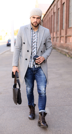 City life. Stylish young man in grey coat and hat walking on the street in the city
