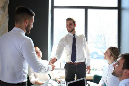 Businessman shaking hands to seal a deal with his partner and colleagues in office Stock Photo