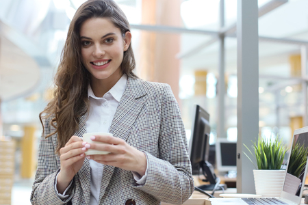 Attractive smiling businesswoman standing in the office with a cup of coffee
