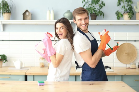 Young happy couple is having fun while doing cleaning at home