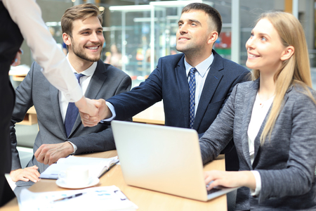 Welcome to our team. Young modern businessmen shaking hands while working in the creative office Stock Photo