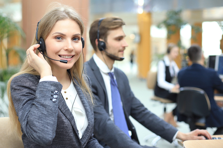 Operador de soporte al cliente femenino con auriculares y sonriendo Foto de archivo