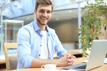 Portrait of young man sitting at his desk in the office Imagens