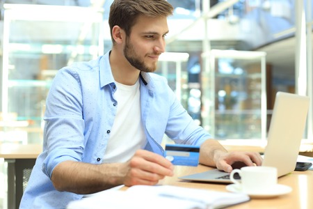 Smiling man sitting in office and pays by credit card with his laptop