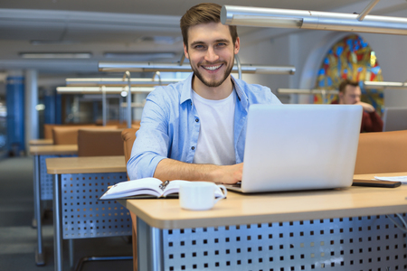 Young student working on laptop in library