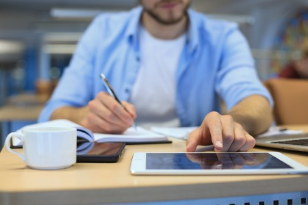 Man writing work plan with pen on paper notebook, browsing internet on digital tablet on office desk