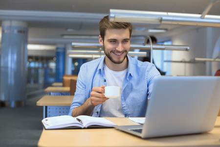 young man drinking coffee in office while typing on laptop Imagens