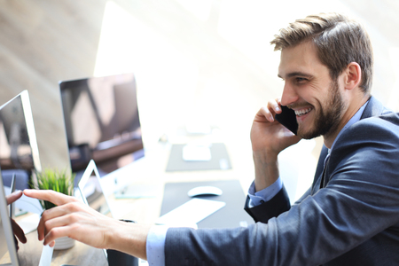 Modern businessman analyzing data using computer and talking on the phone while sitting in the office Imagens