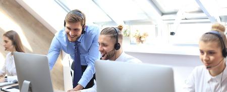 Opérateur téléphonique travaillant au bureau du centre d'appels aidant son collègue Banque d'images