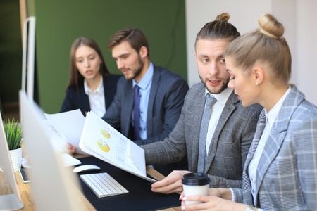 Group of young business people working, communicating while sitting at the office desk together with colleagues