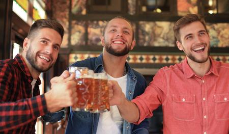 Fußball gucken in der Bar. Fröhliche Freunde trinken Bier und jubeln für die Lieblingsmannschaft, feiern den Sieg