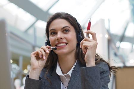 Operador de soporte al cliente femenino con auriculares y sonriendo