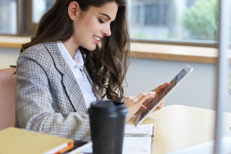 Young smiling businesswoman in office working on digital tablet Imagens