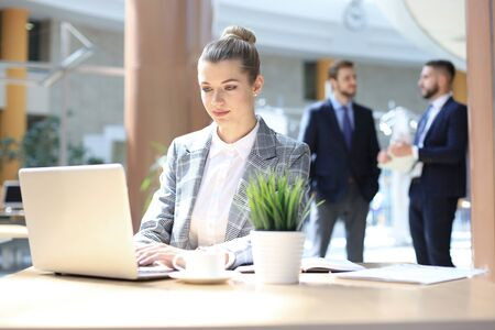 Portrait of a young blond business woman using computer at office.