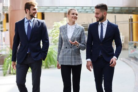 grupa biznesmenów spacerująca po nowoczesnym, jasnym wnętrzu biurowym