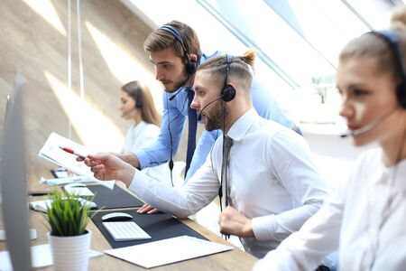 Phone operator working at call centre office helping hiss colleague