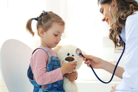 Little girl at the doctor for a checkup. Doctor playfully checking the heart beat of a teddy bear