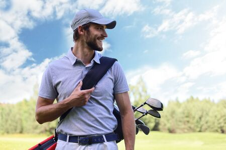 Portrait of male golfer carrying golf bag while walking by green grass of golf club