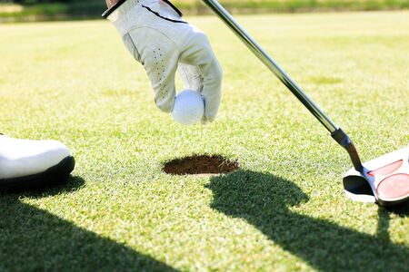 Golf player takes the ball out of the hole