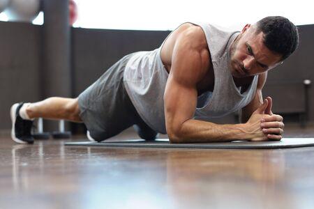 Portret mężczyzny fitness robi ćwiczenie deski w siłowni