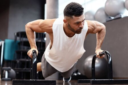 Fit and muscular man doing horizontal push-ups with bars in gym