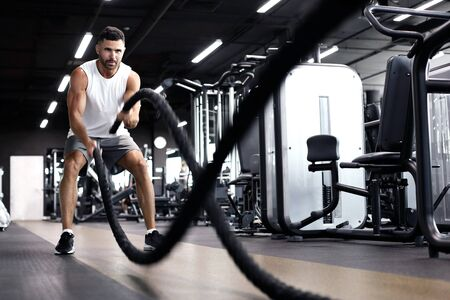 Giovane atletico con corda da battaglia che fa esercizio in palestra per l'allenamento funzionale