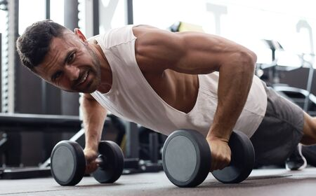 Fit and muscular man doing horizontal push-ups with dumbbells in gym