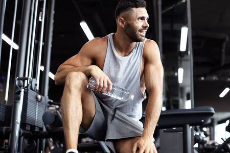 Sporty man resting, having break drinking water after doing exercise