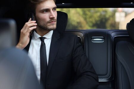 Thoughtful confident businessman talking on the phone while sitting in the car