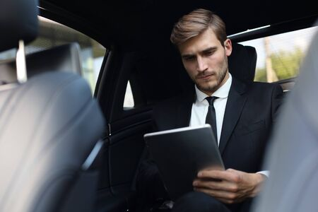Thoughtful confident businessman sitting in the luxe car and using his tablet.