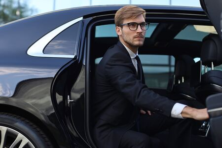 Handsome serious young businessman sitting into his comfortable new car and going to the office.