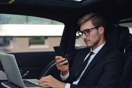 Bel homme confiant en costume complet regardant son téléphone intelligent assis dans la voiture et utilisant un ordinateur portable.