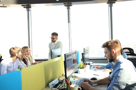 Young modern colleagues in smart casual wear working together while spending time in the creative office
