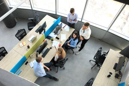 Top view of young modern colleagues in smart casual wear working together while spending time in the office